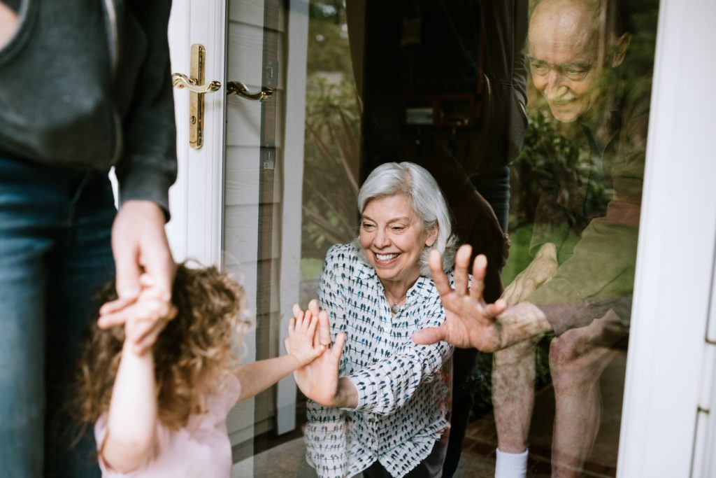 Mother with her daughter, visiting senior parents but observing social distancing with a glass door between them. The granddaughter puts her hand up to the glass, the grandfather and grandmother doing the same