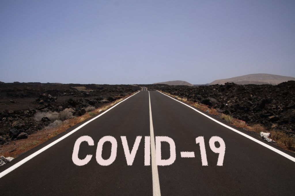 uncertain bleak perspective symbol concept: Endless road through desert with word covid-19