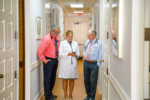 Doctors Raymond James, D.O., Lauren Hana, M.D. and Thomas J. Ervin, M.D. in the hallway at the Boca Grande Health Clinic