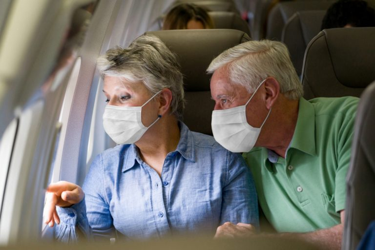 senior couple looking out the window of an airplane