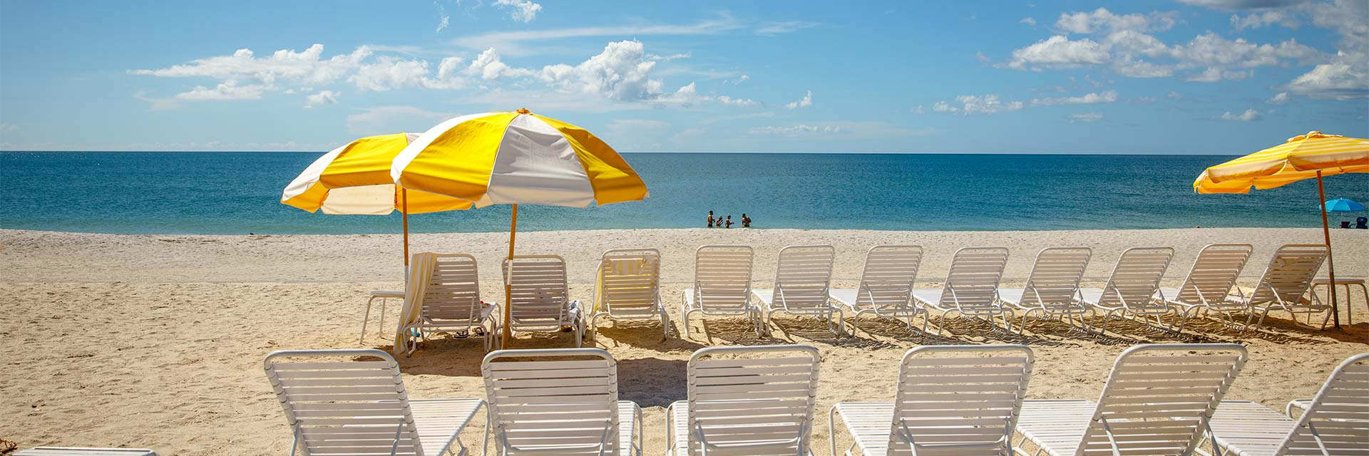beach with yellow umbrellas and chairs at Gasparilla Inn Beach Club