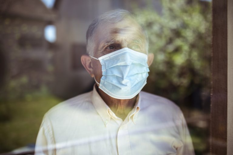 man in a mask looking through a window