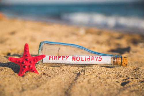 Message reading Happy Holidays in a bottle on the seashore