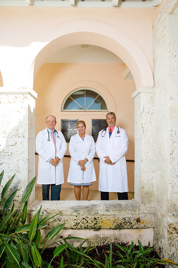 Dr. Ervin, Dr. Hana and Dr. James standing in an archway outside the clinic