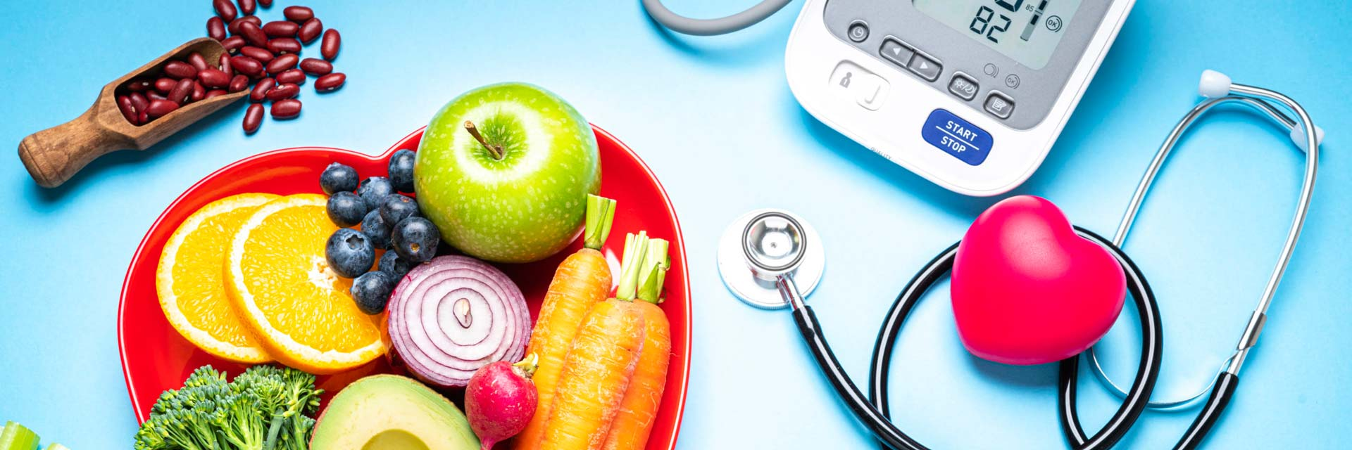Healthy lifestyle concepts: red heart shape plate with fresh fruits and vegetables shot on blue background. A digital blood pressure monitor, doctor stethoscope